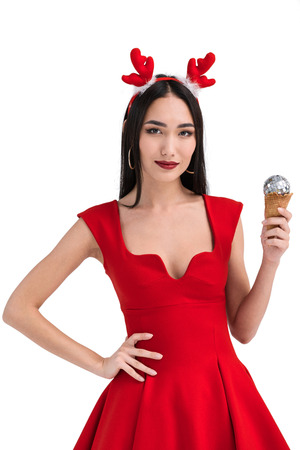 pretty asian woman in deer costume holding ice cream cone with christmas ball isolated on white Stock Photo