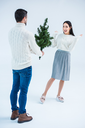 man surprising asian girlfriend with christmas tree isolated on grey