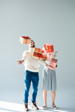 Couple catching falling wrapped christmas presents