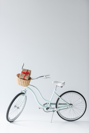 close up view of retro bicycle with wrapped christmas gift in basket isolated on grey
