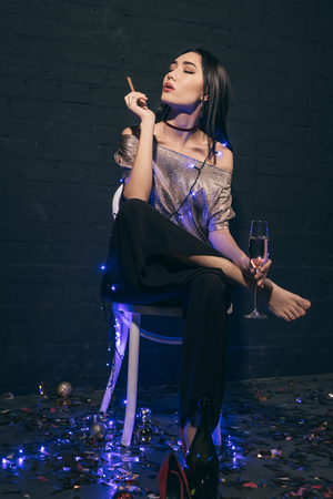 beautiful asian woman in christmas lights with cigar and glass of champagne sitting on chair
