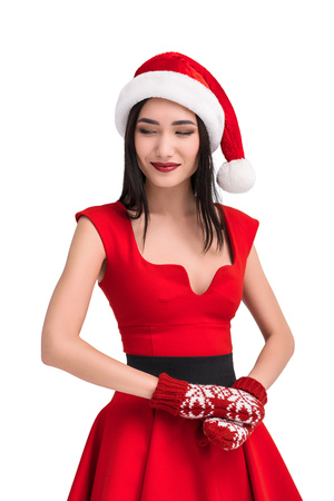 portrait of smiling asian woman in santa costume and mittens isolated on white
