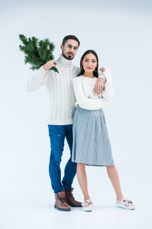 multicultural young couple in sweaters with christmas tree isolated on grey