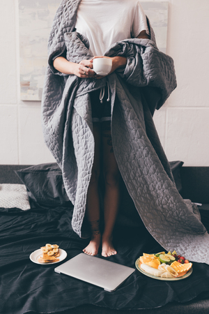 partial view of woman covered in blanket holding cup of coffee while standing on bed at home
