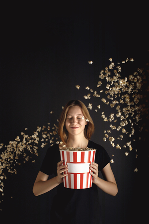 woman with spilling popcorn and bucket in hands isolated on black