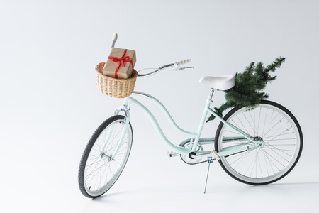close up view of retro bicycle with christmas tree and gift isolated on grey