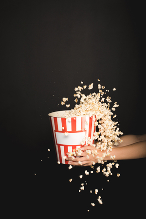 cropped shot of woman holding bucket of spilling popcorn isolated on black 免版税图像