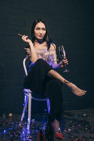 椅子に座っているシャンパンの葉巻とガラスとクリスマスライトで美しいアジアの女性
