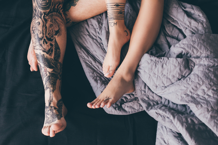 cropped shot of tattooed couple resting in bed together in morning  Stok Fotoğraf