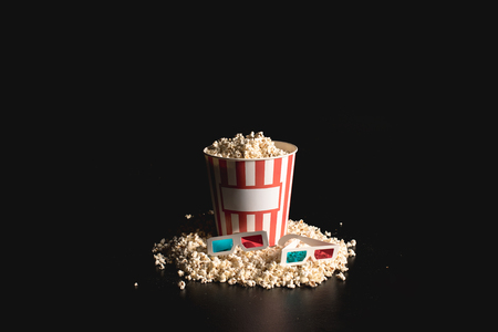box of tasty popcorn with 3d glasses on black Banque d'images