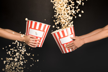 cropped shot of people spilling out popcorn from buckets isolated on black