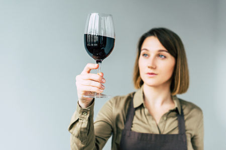 Portrait of Female sommelier examining red wine  Stock Photo