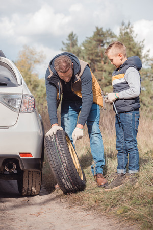 Father and son changing car wheel together in autumn forest