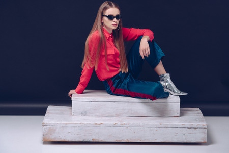 Stylish girl in red shirt and black sunglasses sitting on a wooden stairs  Stock Photo