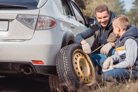 smiling father and son changing car wheel together Stok Fotoğraf