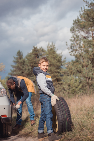 smiling little boy holding tire while changing car wheel with father