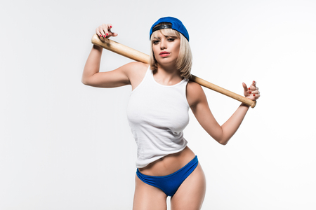portrait of beautiful woman in cap with baseball bat on shoulders looking at camera isolated on white