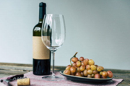 Wine bottle with empty glass and grapes on a wooden table  Фото со стока