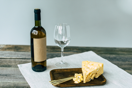 Wine bottle with empty glass and cheese on a wooden table Foto de archivo - 102616195
