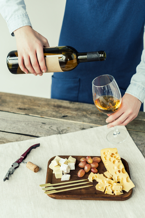 woman in apron pouring white wine into glass