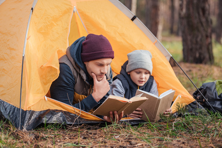 father and son reading books while lying together in tent Stockfoto