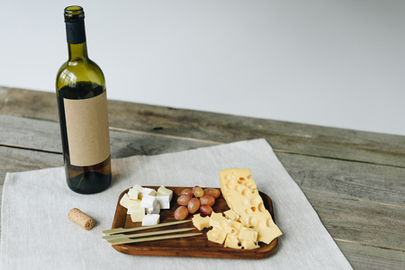 Wine bottle and plate with cheese and grapes on a wooden table Stock Photo