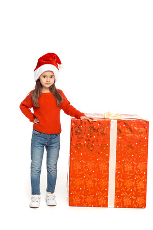 female child in santa hat with big christmas present, isolated on white