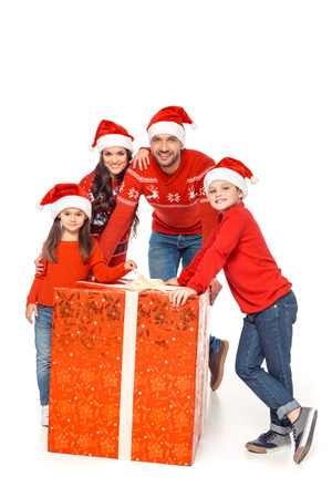 happy family in santa hats with big christmas present, isolated on white Stock Photo