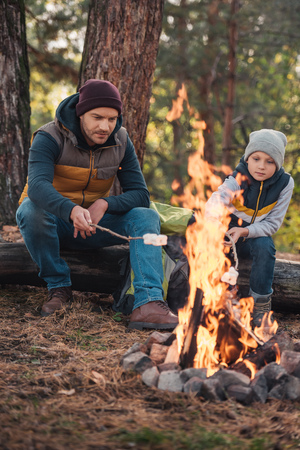 full length view of father and son cooking marshmallows at campfire in autumn forest
