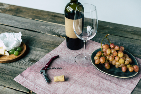 Wine bottle with empty glass and grapes on a wooden suface Фото со стока