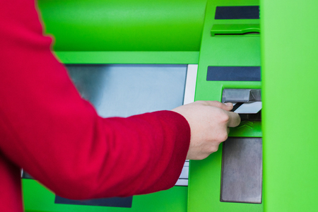 cropped shot of woman putting credit card into atm cash machine Archivio Fotografico - 102615958