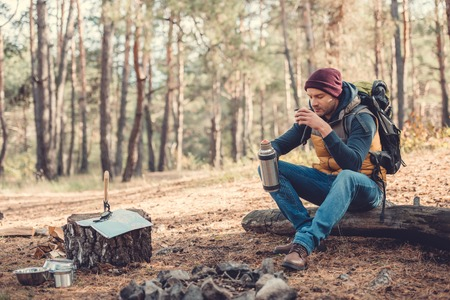 handsome young man with backpack drinking hot tea from thermos while sitting on log in forest Imagens