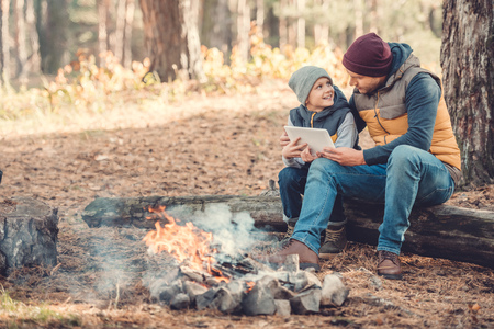 happy father and son using digital tablet while sitting on log in autumn forest