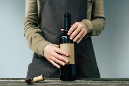 Woman in apron holding open bottle of red wine Фото со стока