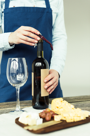 Cropped image of female sommelier opening a bottle of white wine with corkscrew