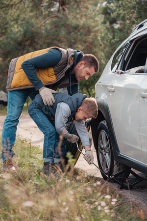 full length view of father and son changing car wheel together in forest
