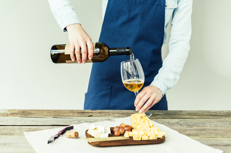 Cropped image of Female sommelier pouring white wine into glass  Фото со стока