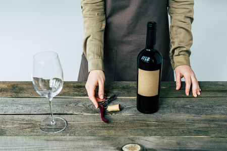 Cropped image of Female sommelier standing with open bottle of red wine