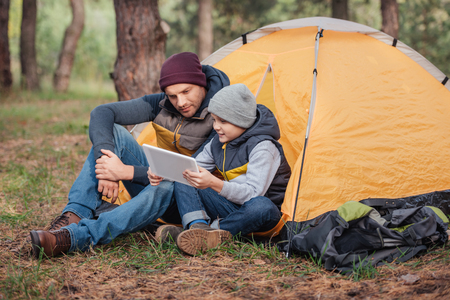 father and son using digital tablet while sitting near tent in autumn forest