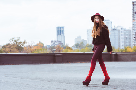 Cute woman in burgundy hat and autumn outfit walking on a building roof