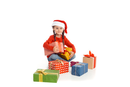 little kid in santa hat with christmas gifts, isolated on white