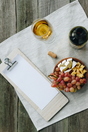 Top view of glass with white wine, plate with cheese and grapes and clipboard