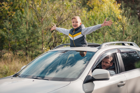 happy little boy with open arms standing in open car sunroof while father driving car in forest
