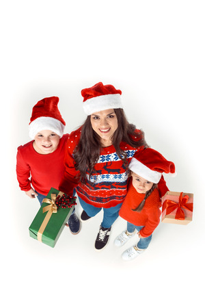 overhead view of mother and children in santa hats with christmas gifts, isolated on white