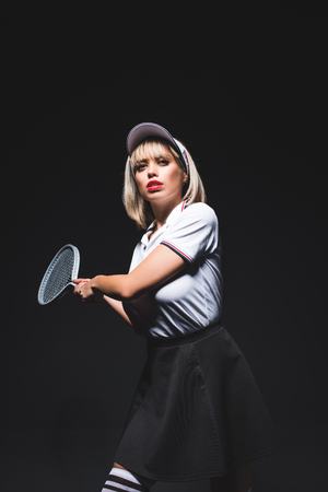 portrait of beautiful woman with tennis racket posing isolated on black 스톡 콘텐츠