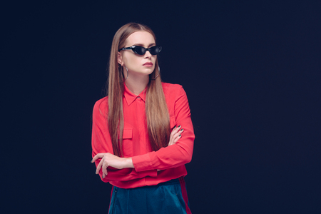 Beautiful woman in red shirt and black sunglasses standing isolated on black