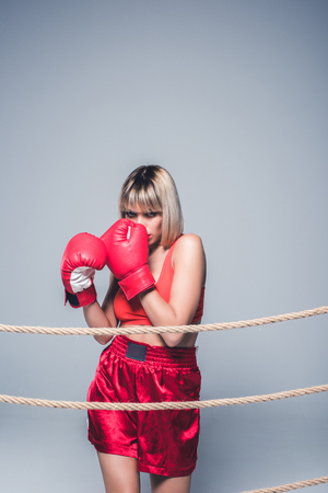 portrait of beautiful woman in sportswear and boxing gloves posing isolated on grey