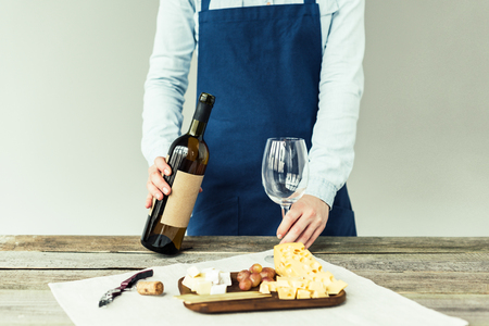 Cropped image of female sommelier holding bottle of white wine and empty glass