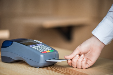 cropped shot of woman putting credit card into edc machine