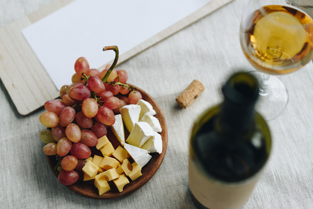 glass with white wine, grapes and cheese and clipboard